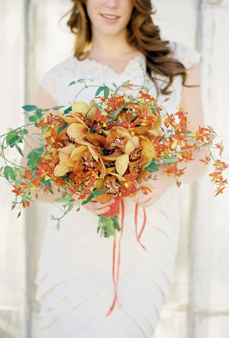 Fall wedding bouquet made of orange cymbidium orchids and greenery - Wedding Belles Blog