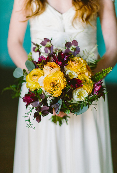 Yellow and plum wedding bouquet made with ranunculus, antique garden roses, helleborus, parrot tulips, godetia, astilbe, silver dollar eucalyptus, sea star ferns, sword ferns, and jasmine vine - Wedding Belles Blog