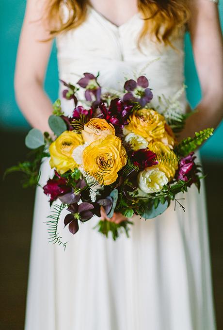Yellow and plum wedding bouquet made with ranunculus, antique garden roses, helleborus, parrot tulips, godetia, astilbe, silver dollar eucalyptus, sea star ferns, sword ferns, and jasmine vine - Wedding Belles Blog